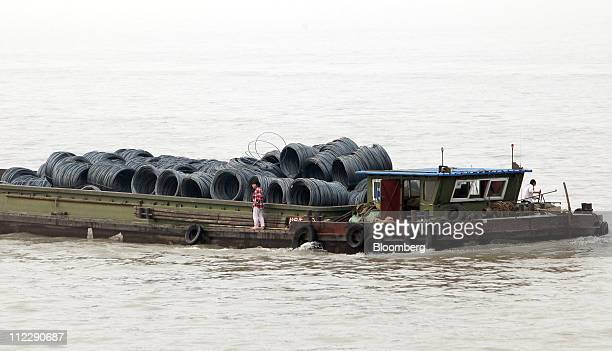A boat sails past the dock of the Baosteel Group Corp facilities in Shanghai China on Friday April 15 2011 Baosteel Group is the supplier of half the...