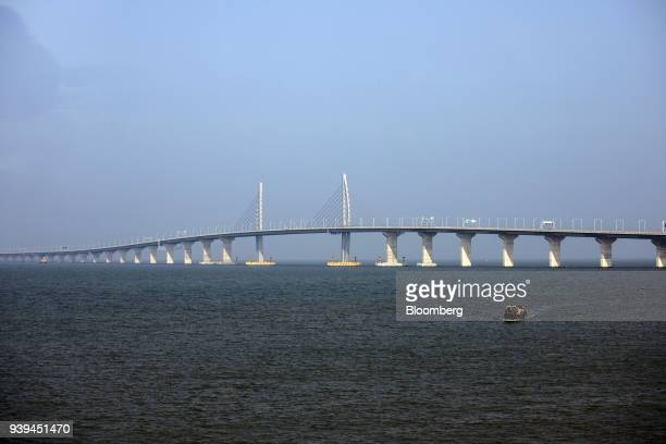 A boat sails towards a section of the Hong KongZhuhaiMacau Bridge standing offshore in Zhuhai China on Wednesday March 28 2018 The multibillion...