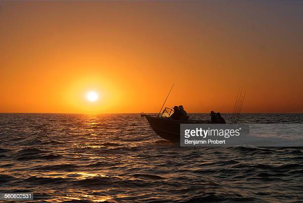 Boat silhouette on ocean with sunrise