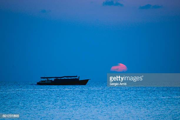 Boat silohuetted against a pink sunset