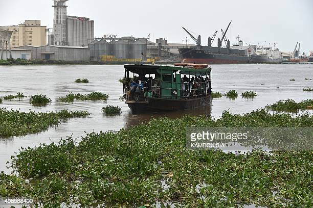 A boat taking commuters from Abidjan's Plateau business district to the popular area of Yopougon sails on the Ebrie lagoon partially choked with...