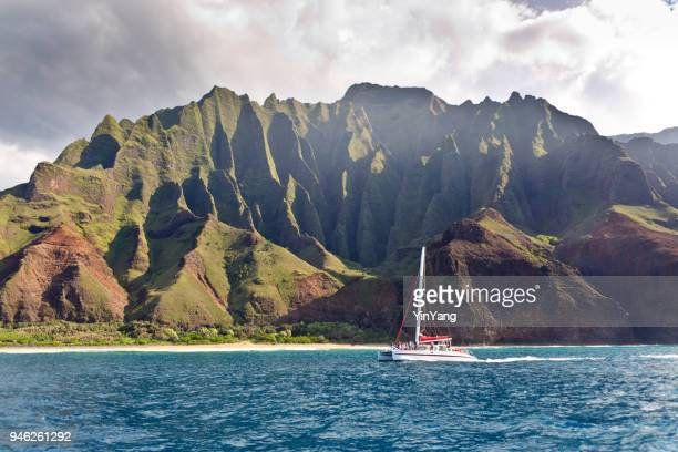 boat tour on scenic landscape of na pali coast of kauai, hawaii - catamaran stock photos and pictures
