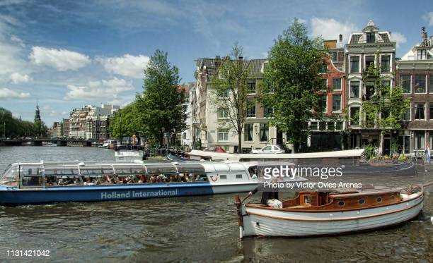 boat tours on the river amstel and the munttoren clock tower in muntplein square in amsterdam, netherlands - victor ovies fotografías e imágenes de stock