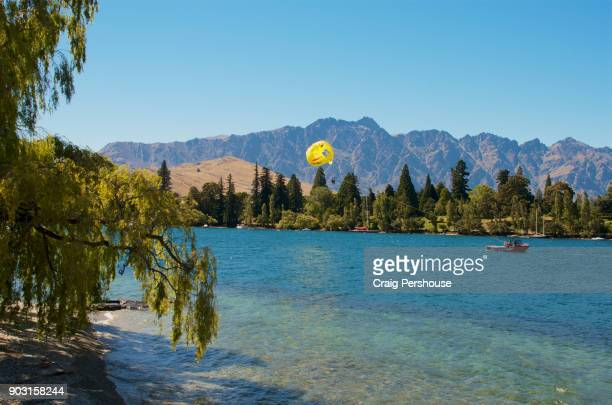Boat towing parasailers above Queenstown Bay, with The Remarkables mountain range towering behind.