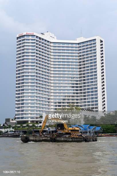 Boat transporting an excavator seen front of the Sheraton Hotel at Chao Phraya River, Bangkok, Thailand. Daily life in Bangkok capital of Thailand.