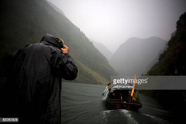 A boat travels along the Yangtze River on part of the river responsible for the forced relocation of residents whose homes are being intentionally...