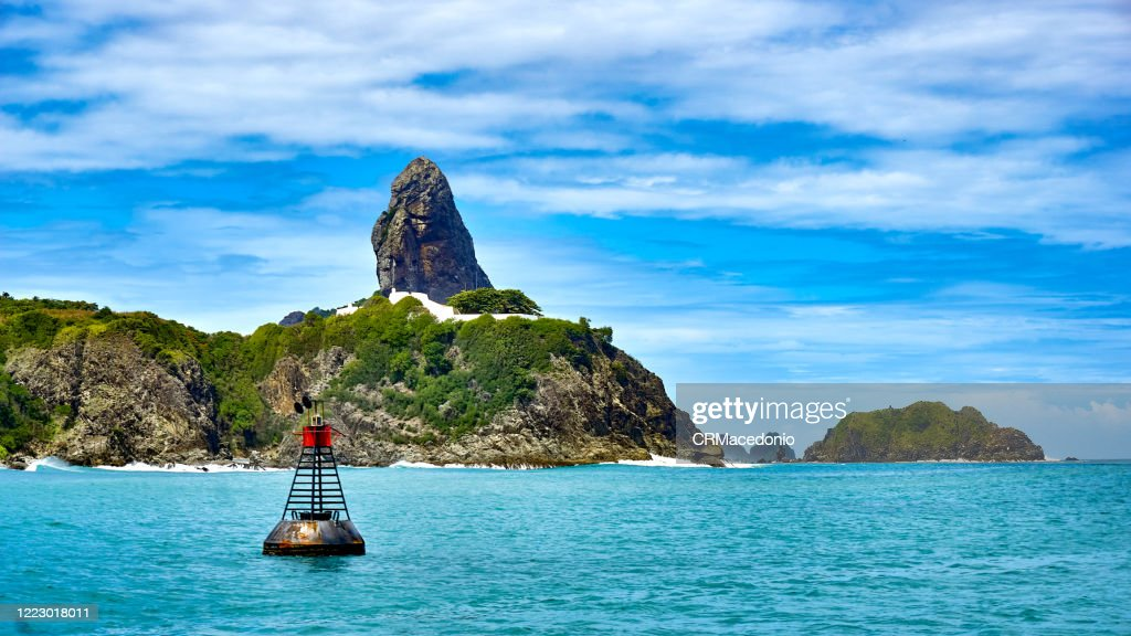 Boat trip through the Bay of Santo Antonio. A signal buoy in front of us. In the background, Fort Nossa Senhora dos Remédios, Morro do Pico and Morro Dois Irmãos. : Stock Photo