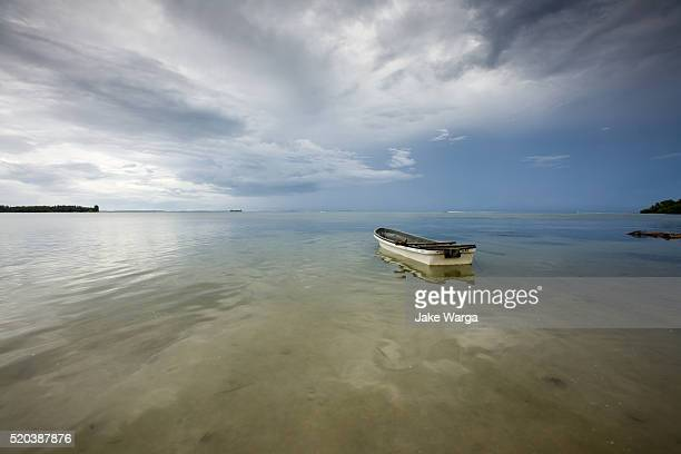 boat under stormy sky, kavieng, papua new guinea - jake warga stock pictures, royalty-free photos & images