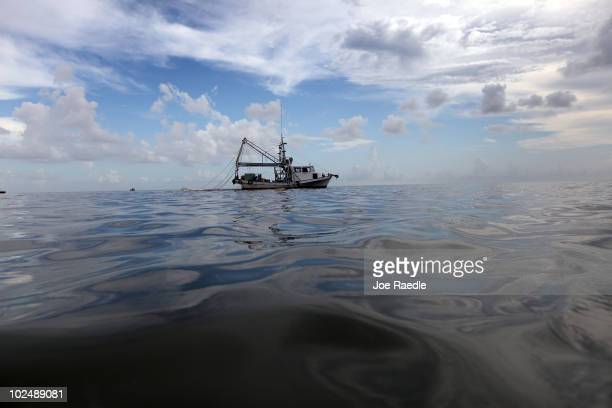 A boat uses a boom and absorbent material to soak up oil on the surface of the water from the Deepwater Horizon oil spill in the Gulf of Mexico in...