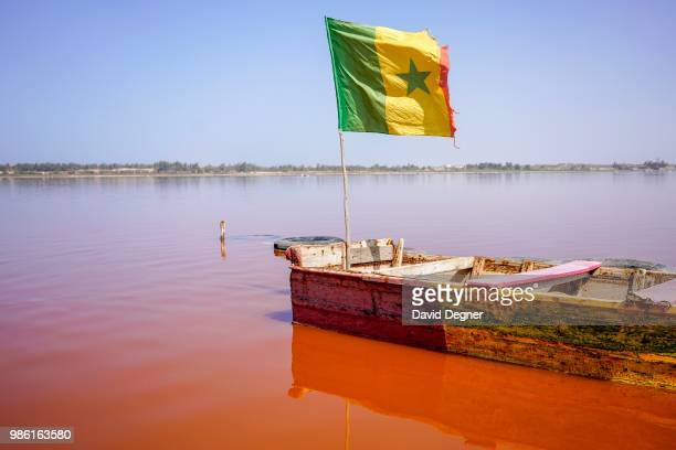 Boat with a Senegalese flag floats on Lac Rose on the edge of Dakar, Senegal. Lac Rose is a saline lake that gets its color from a special type of...