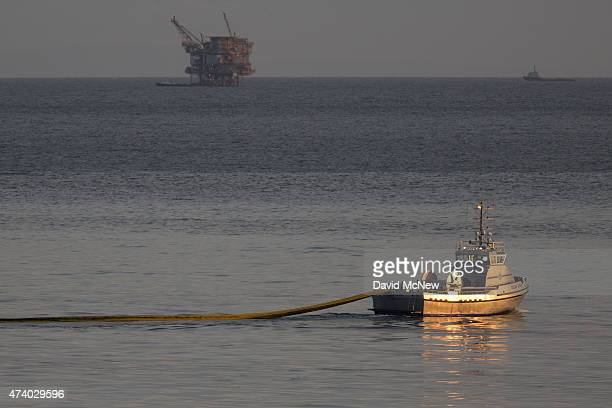A boat with the nonprofit collective Clean Seas deploys a boom with an oil platform seen in the distance to try to contain an oil spill on May 19...