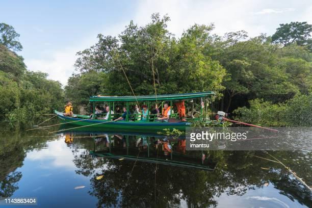 bateau avec des touristes sur le tributaire de la rivière rio negro - piranha photos et images de collection