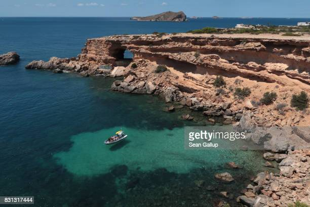 A boat with visitors stops at a quiet cove on the island of Ibiza on August 10 2017 near Sant Antoni Spain Ibiza is a popular tourist destination