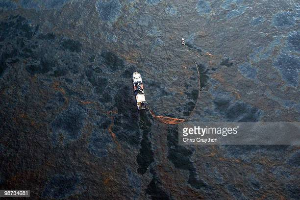 A boat works to collect oil that has leaked from the Deepwater Horizon wellhead in the Gulf of Mexico on April 28 2010 near New Orleans Louisiana An...