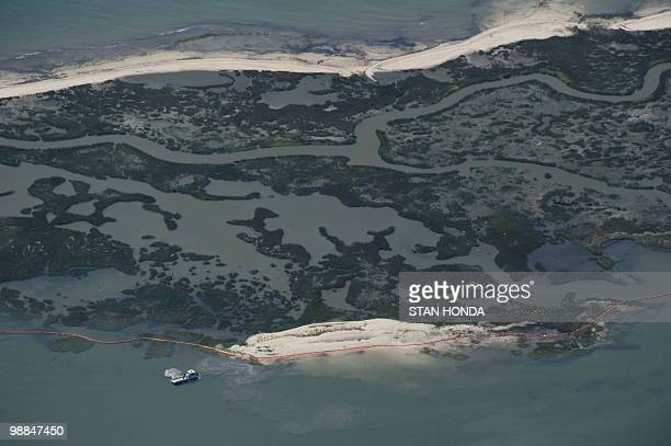 A boat works to lay orange oil booms May 4 2010 around one of the Chandeleur Islands off Louisiana as the gulf coast is still being threatened by the...