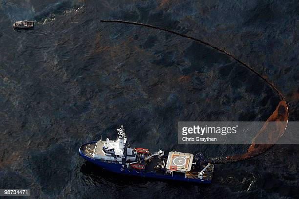 A boat works uses a protective boom to collect oil that has leaked from the Deepwater Horizon wellhead in the Gulf of Mexico on April 28 2010 near...
