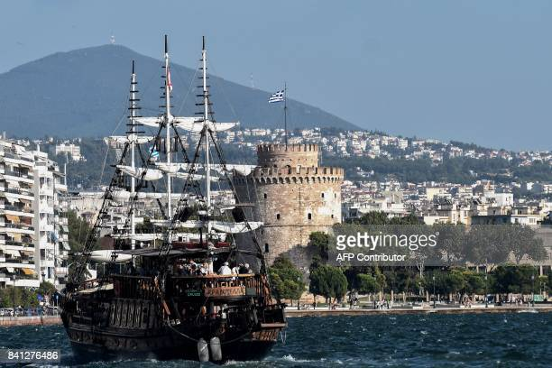 A boatbar sails past the White Tower in the Thermaikos gulf in Thessaloniki on August 31 2017 Near The White Tower on the edge of the harbor front of...
