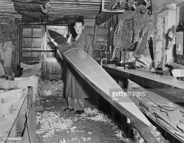 Boatbuilder George Sims carrying a racing shell which he has completed for the United States rowing team for use at the 1956 Summer Olympics at his...