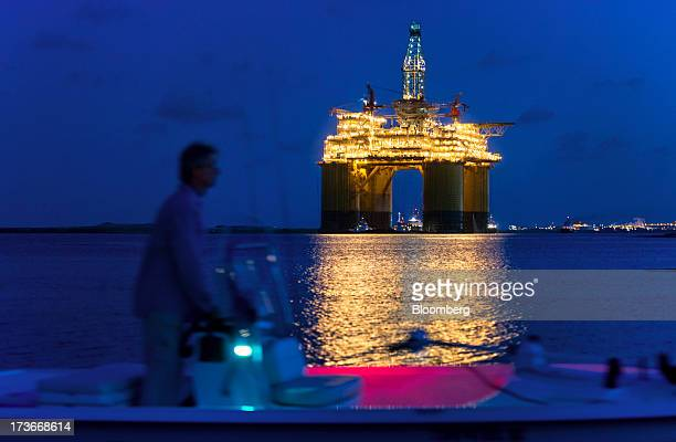 A boater passes the Royal Dutch Shell Plc Olympus tension leg platform at dawn as it sets sail from Kiewit Offshore Services in Ingleside Texas US on...