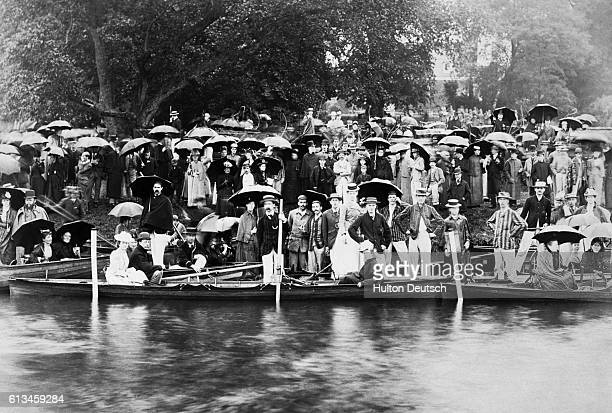 Boaters in punts and along shore posing for group portrait. | Location: Cambridge, England, UK.