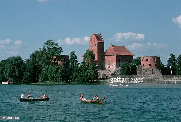 Boaters row across Lake Galve towards the restored 15th century castle of Trakai the former capital of Lithuania