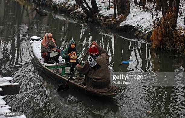 A boatman amid sub zero temperatures takes a ride in Dal Lake considered a major tourist attraction in Indian Controlled Kashmir with his family