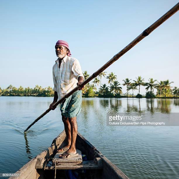 Boatman guiding boat through Keralan backwaters, North Paravoor, Kerala, India