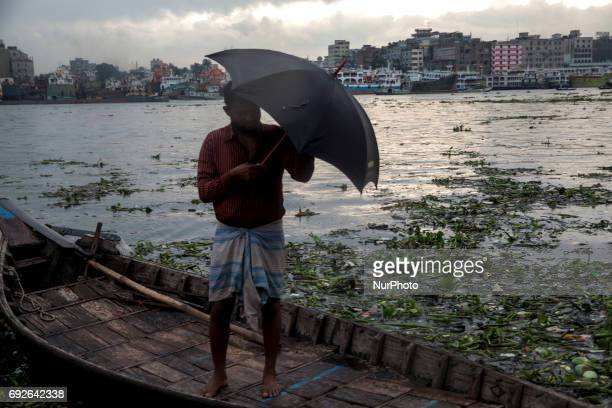 A boatman holds his umbrella and waiting to the passenger near the riverbank of Buriganga on the eve of World Environment Day in Dhaka Bangladesh 05...