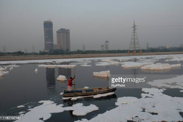 Boatman navigates in polluted waters of Yamuna River filled with toxic foam on a smoggy evening in New Delhi on 4th November, 2019.