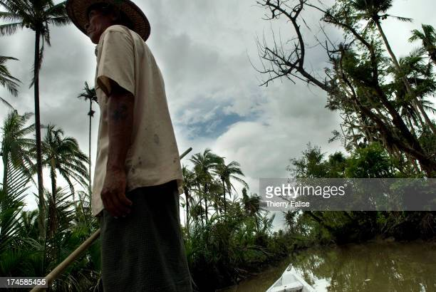 A boatman pushes his boat up a narrow subsidiary of the Irrawaddy River According to official figures the cyclone killed about 140000 people on May 2...