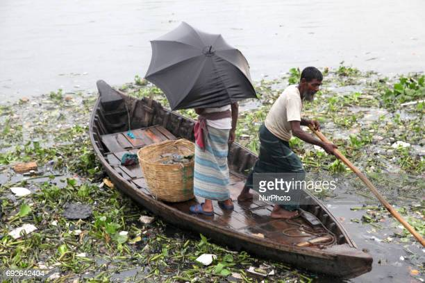 A boatman ride his boat with passenger in the polluted water near the riverbank of Buriganga on the eve of World Environment Day in Dhaka Bangladesh...