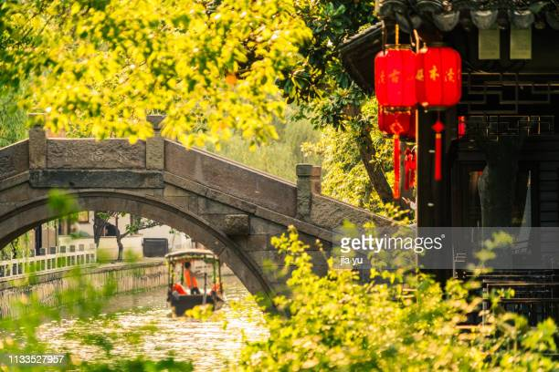 boatman rowing on canal travel through an arch bridge - suzhou stock pictures, royalty-free photos & images
