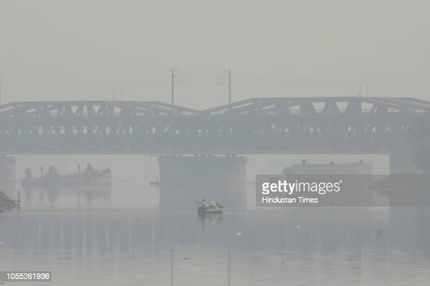 A boatman rows his boat amid a thick layer of smog at Yamuna Nigambodh Ghat on October 29 2018 in New Delhi India The Central Pollution Control Board...