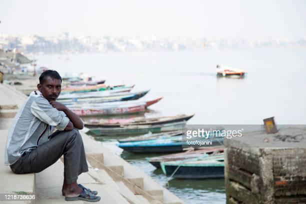 ガンジス川のほとりで顧客を待っているボートマン - fotofojanini ストックフォトと画像