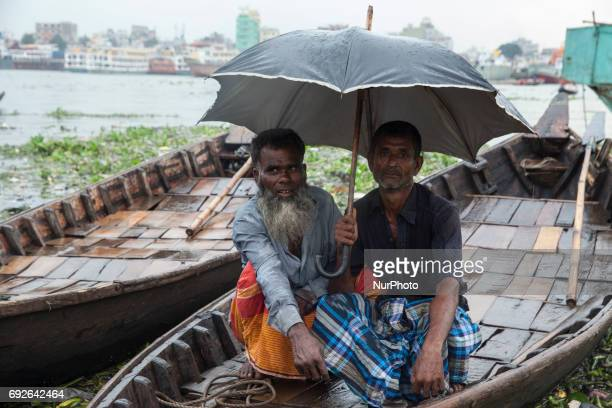 A boatmans sit on the boat to waiting for a passengers near the riverbank of Buriganga on the eve of World Environment Day in Dhaka Bangladesh 05...