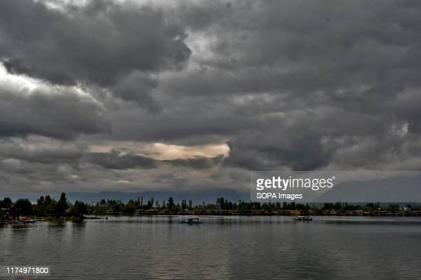 Boatmen row their boats on Dal lake during a cloudy day in Srinagar.