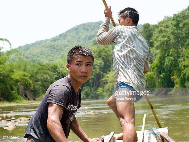 Boatmen Savath and Sengkham navigate their boat up the Nam Ou river using bamboo poles during the dry season when the river level is low Phongsaly...