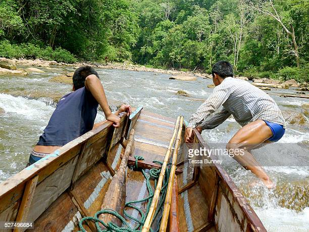 Boatmen Savath and Sengkham pull their boat up the rapids on the Nam Ou river during the dry season when the river level is low Phongsaly province...