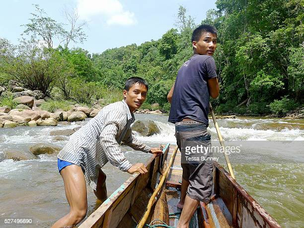 Boatmen Sengkham and Savath navigate their boat up the rapids on the Nam Ou river during the dry season when the river level is low Phongsaly...
