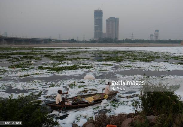 Boatmen struggle to navigate in polluted waters of Yamuna River filled with toxic foam on a smoggy evening in New Delhi on 4th November, 2019.