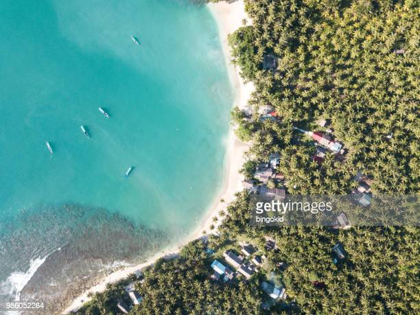 Boats anchored in a small bay next to a small tropical village (aerial)
