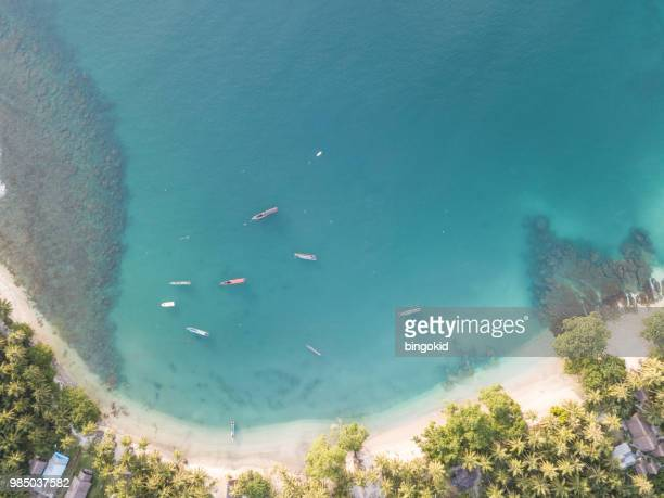Boats anchored in a small bay next to a tropical island from above