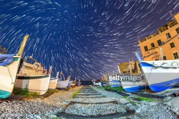 Boats And Buildings Against Star Trails