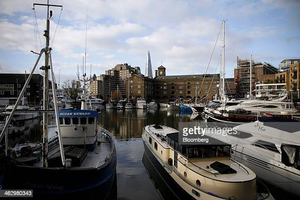 Boats and luxury yachts sit moored to berths in St Katherine docks close to the former News International newspaper site in Wapping London UK on...