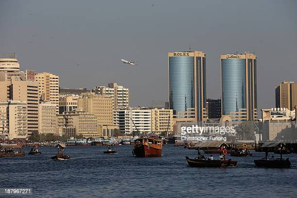 Boats and water taxis make their way along Dubai Creek as an Emirates passenger aircraft takes off from Dubai International Airport on November 13...