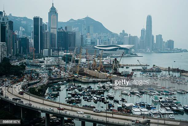 Boats and yachts sit moored in a bay near the construction of the Wan Chai Bypass Project as vehicles travel along the Island Easter Corridor...