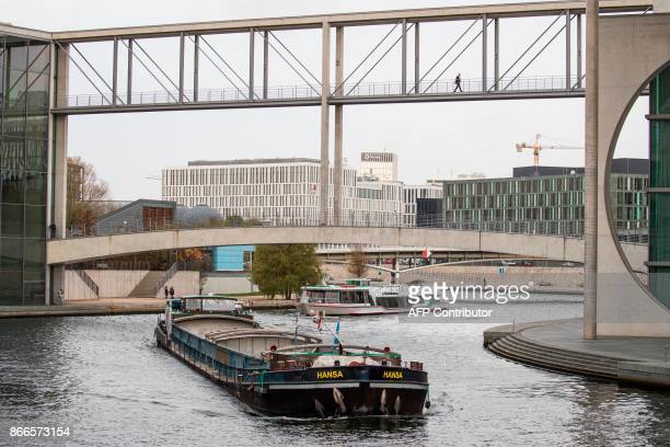 Boats are making their way where river Spree cuts through the government quarters in Berlin on October 26 2017 / AFP PHOTO / Odd ANDERSEN