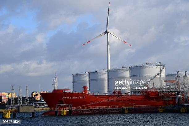 Boats are moored at docks next to a wind turbine in the Port of Antwerp on January 17 2018 / AFP PHOTO / EMMANUEL DUNAND