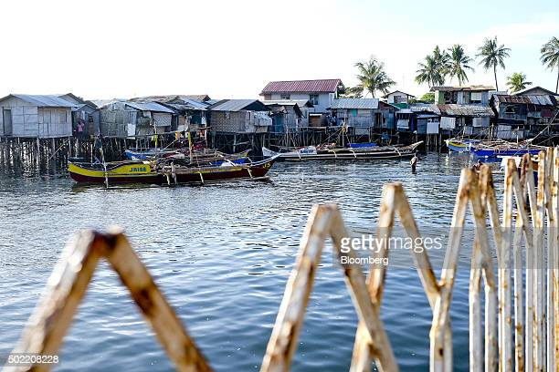 Boats are moored in front of houses on stilts in the Isla Verde shantytown of Davao Mindanao the Philippines on Friday Dec 11 2015 Davao city's...