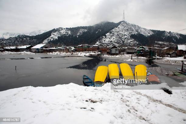 Boats are moored to the bank of Dal lake after a snowfall on January 23 2014 in Srinagar Indian Administered Kashmir India Cold weather continued in...